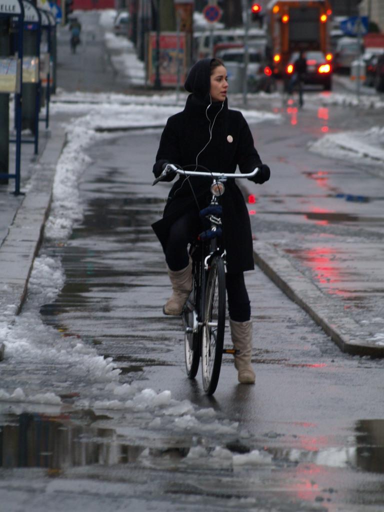 Frau am Fahrrad bei Schnee in Wien