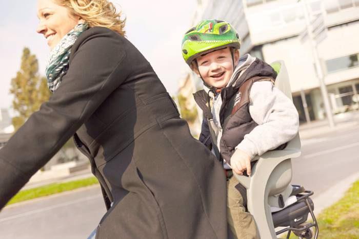 Eine blonde Frau fährt mit dem Fahrrad. Auf dem Kindersitz hinter ihr sitzt ein BUb. Er trägt einen Helm und lächelt.