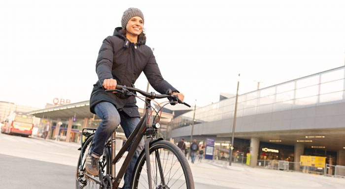 Junge Frau fährt auf ihrem Fahrrad, begleitet mit Winterjacke und Haube, am Hauptbahnhof vorbei. Foto von Stephan Doleschal.