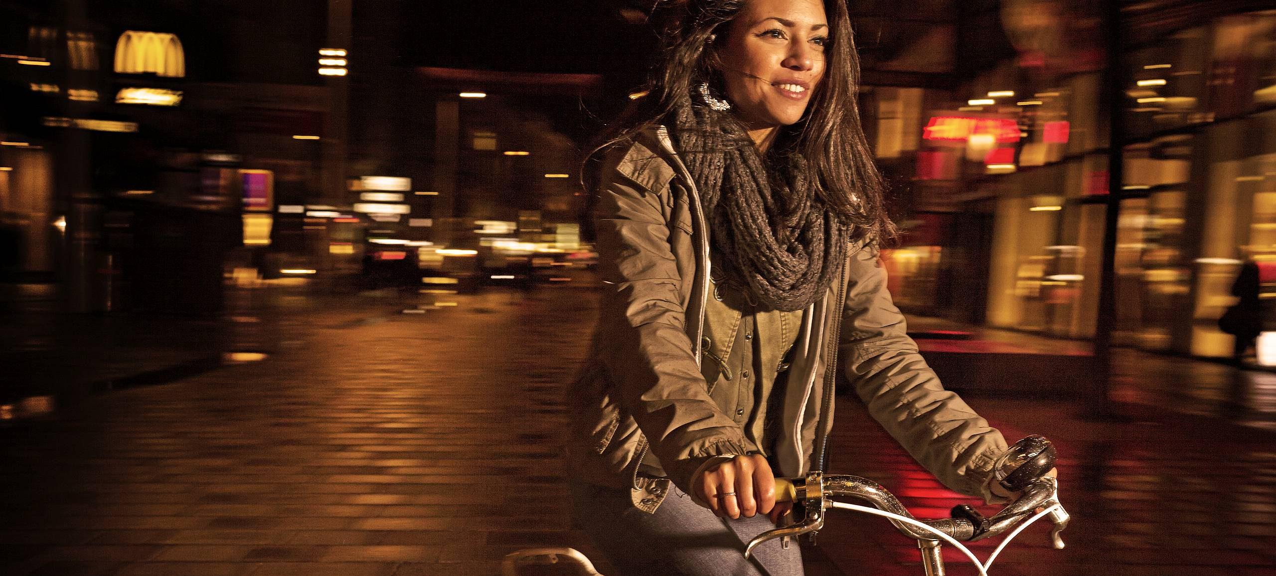 Eine junge Radfahrerin fährt nachts im 8. Bezirk.