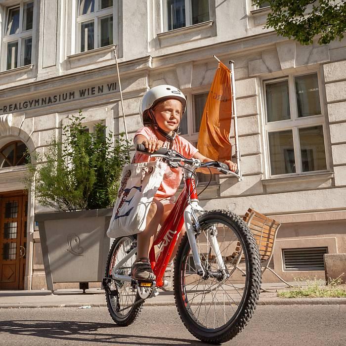Ein junges Mädchen mit Helm übt das Radfahren im 7. Bezirk.