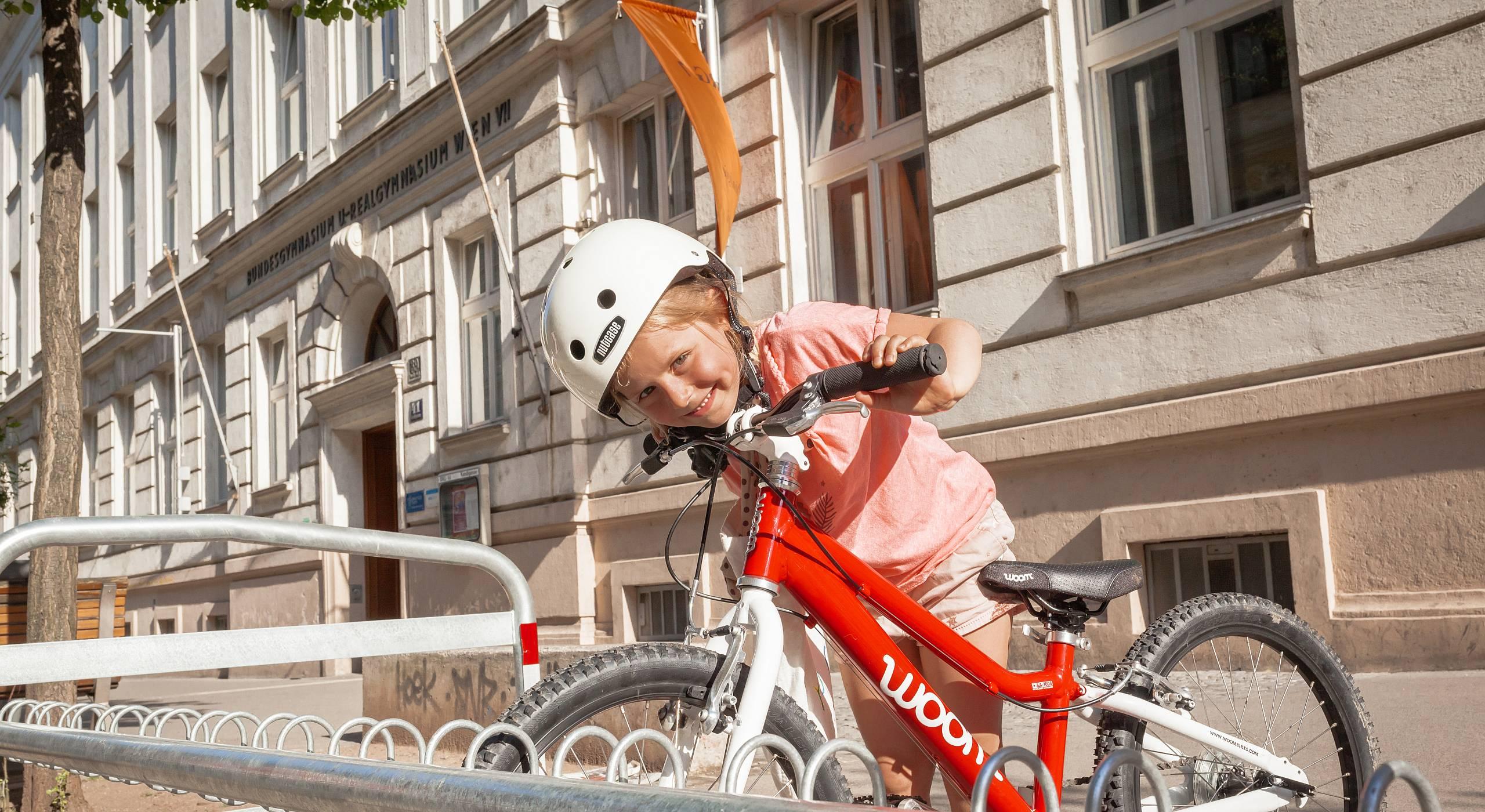 Ein kleines Mädchen schiebt ihr Rad zu einem Fahrradständer und grinst verschmitzt in die Kamera.