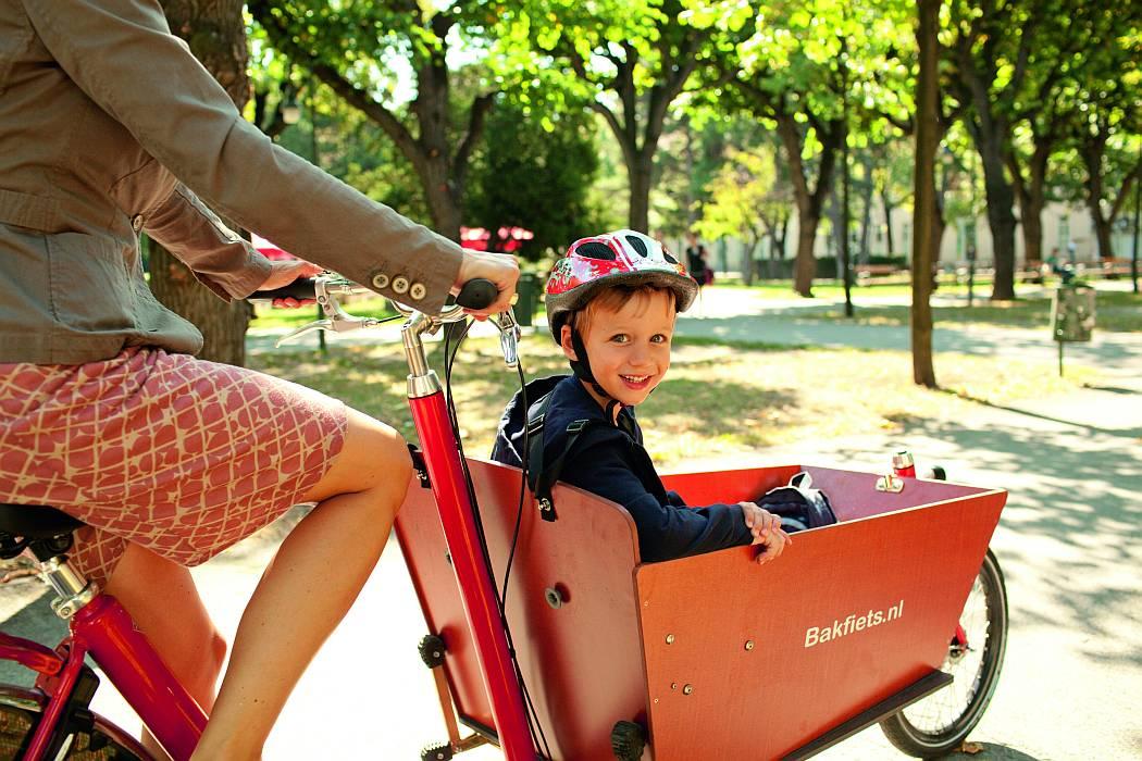 Ein junger Bub sitzt lächeln im Lasenrad seiner Mutter.