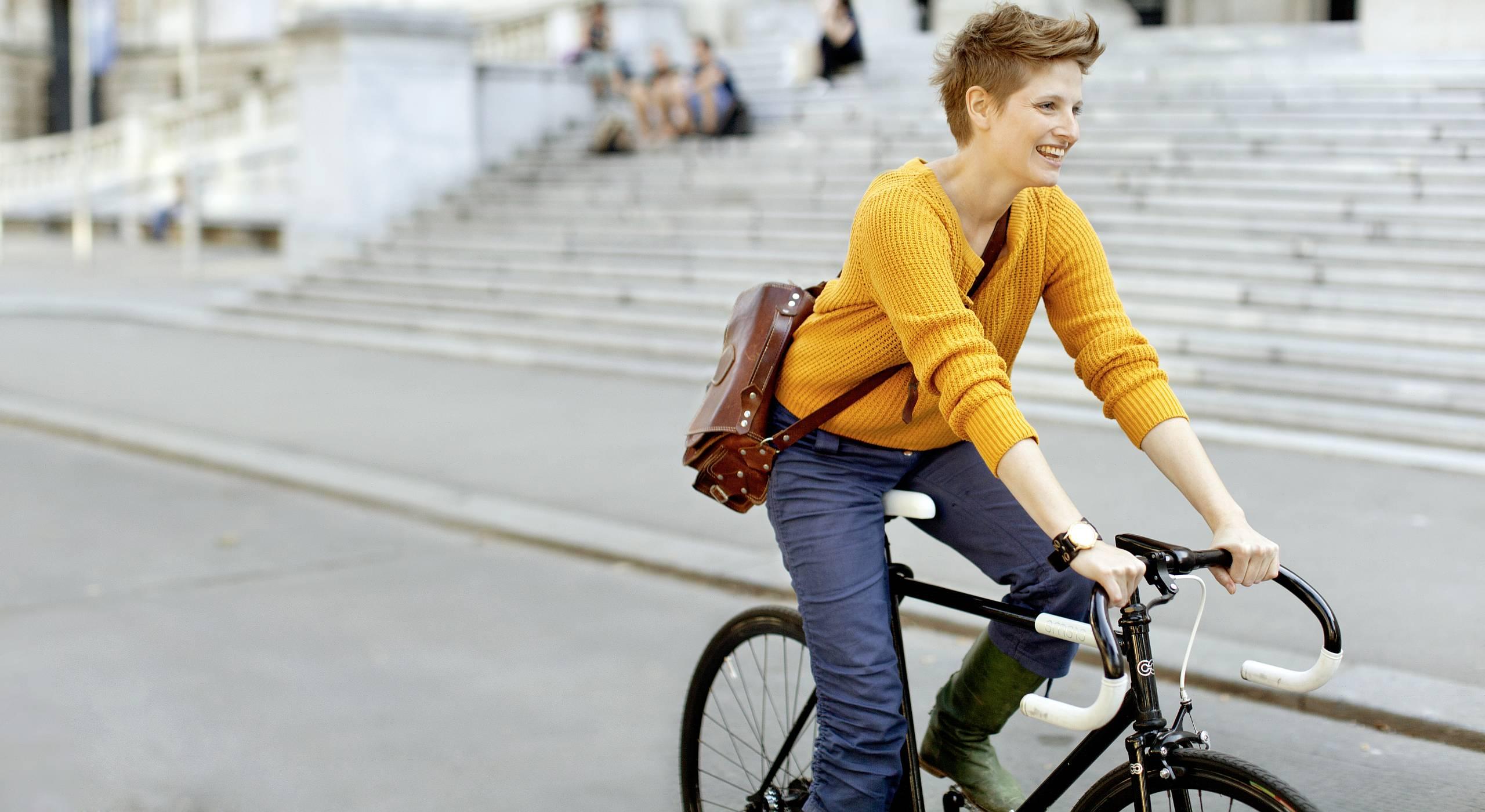 Eine junge Frau mit Kurzhaarschnitt radelt an der Wiener Hauptuni vorbei.