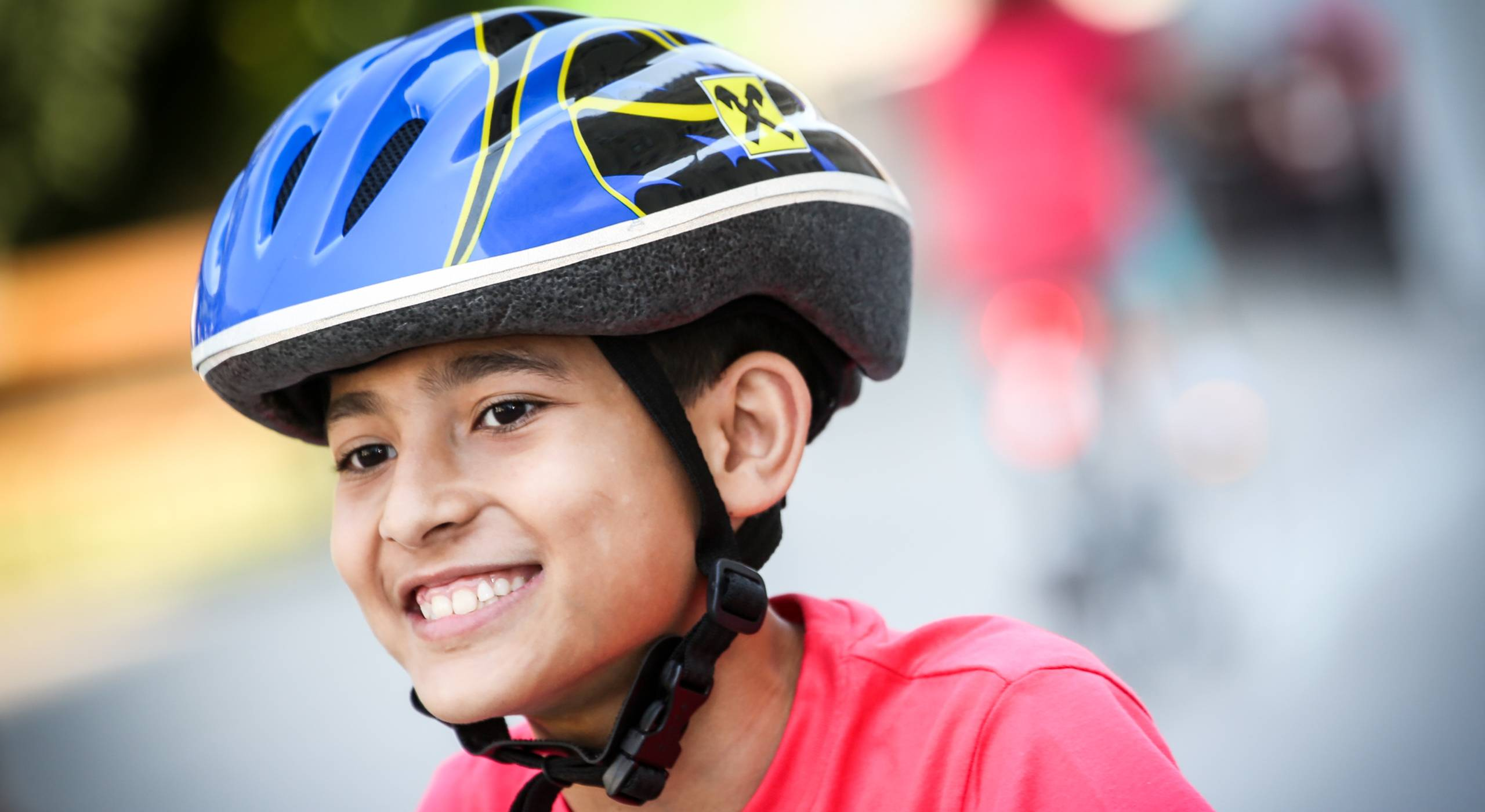 Portrait eines Buben der einen Fahrrad-Helm trägt. Foto von Christian Fürthner