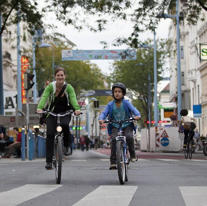 Mutter und Sohn radeln die Mariahilferstraße entlang.