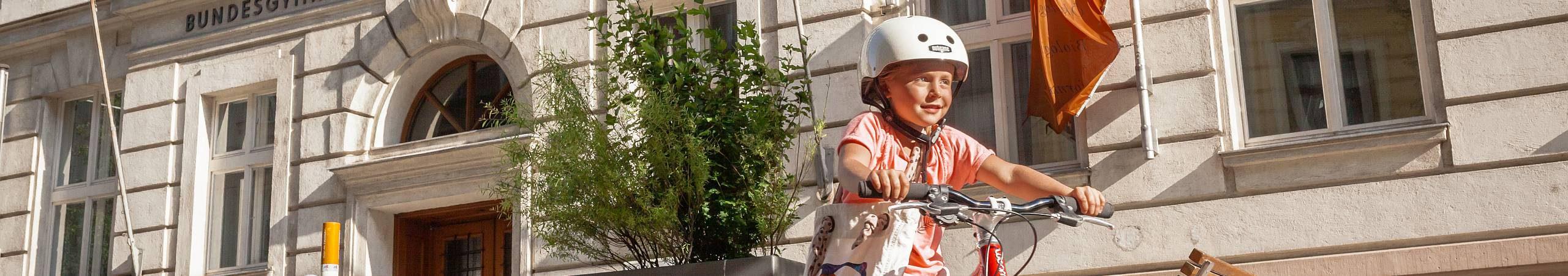 Ein junges Mädchen übt an einem sonnigen Tag das Fahrradfahren.