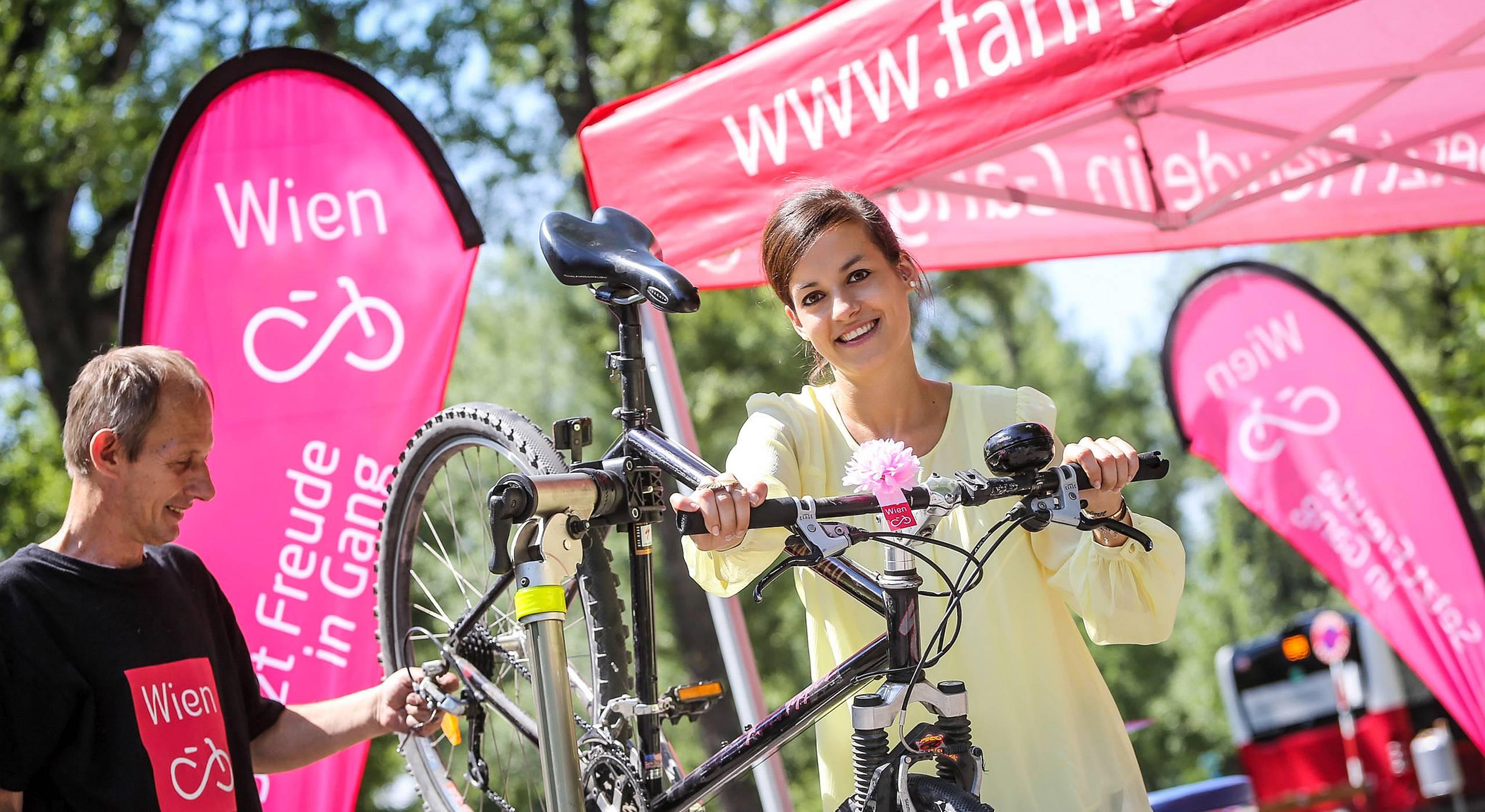 Eine junge Frau freut sich über ihr frisch serviciertes Rad.