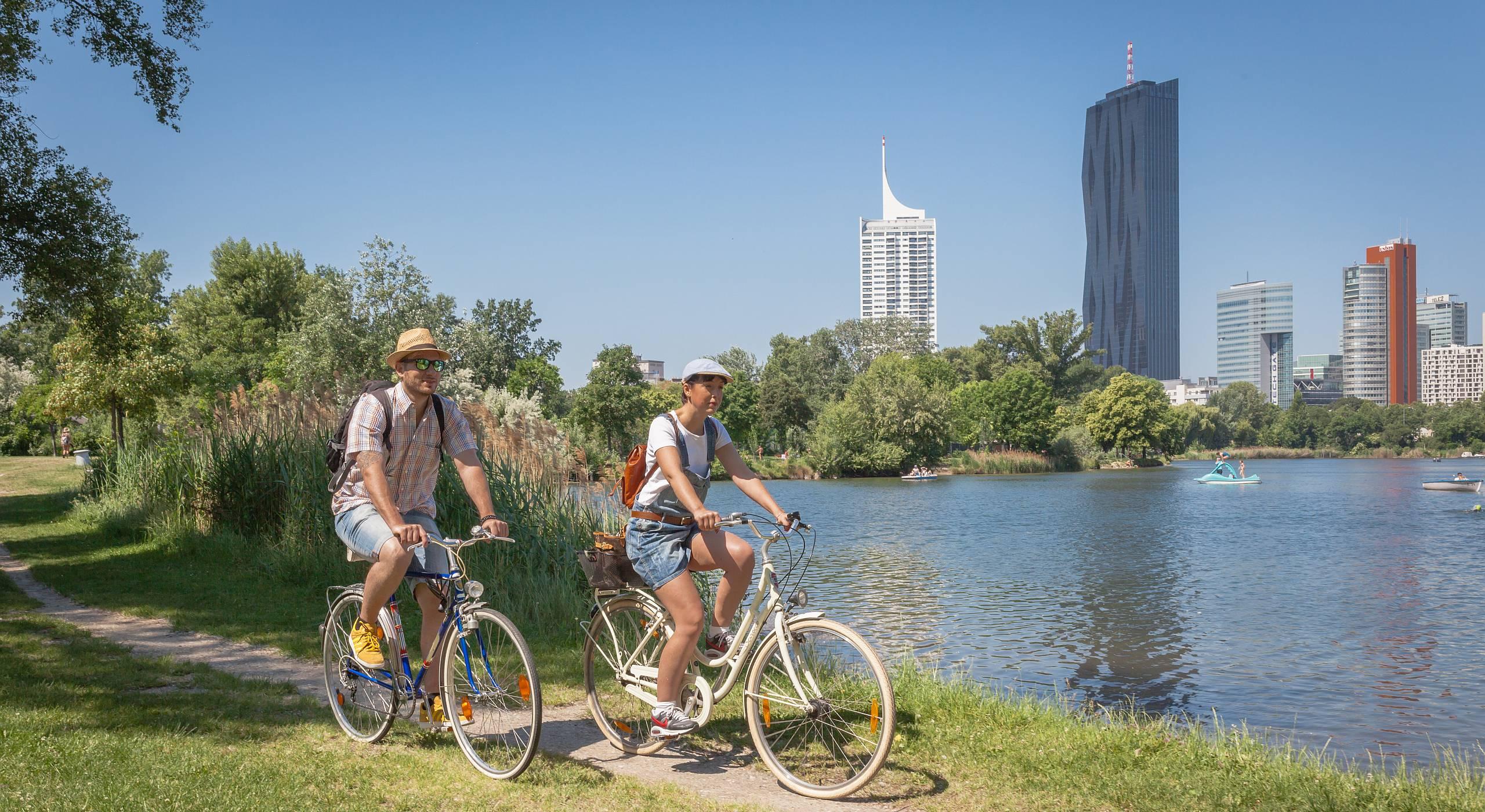 Ein junges Paar radelt an einem sonnigen Junitag am Kaiserwasser entlang.