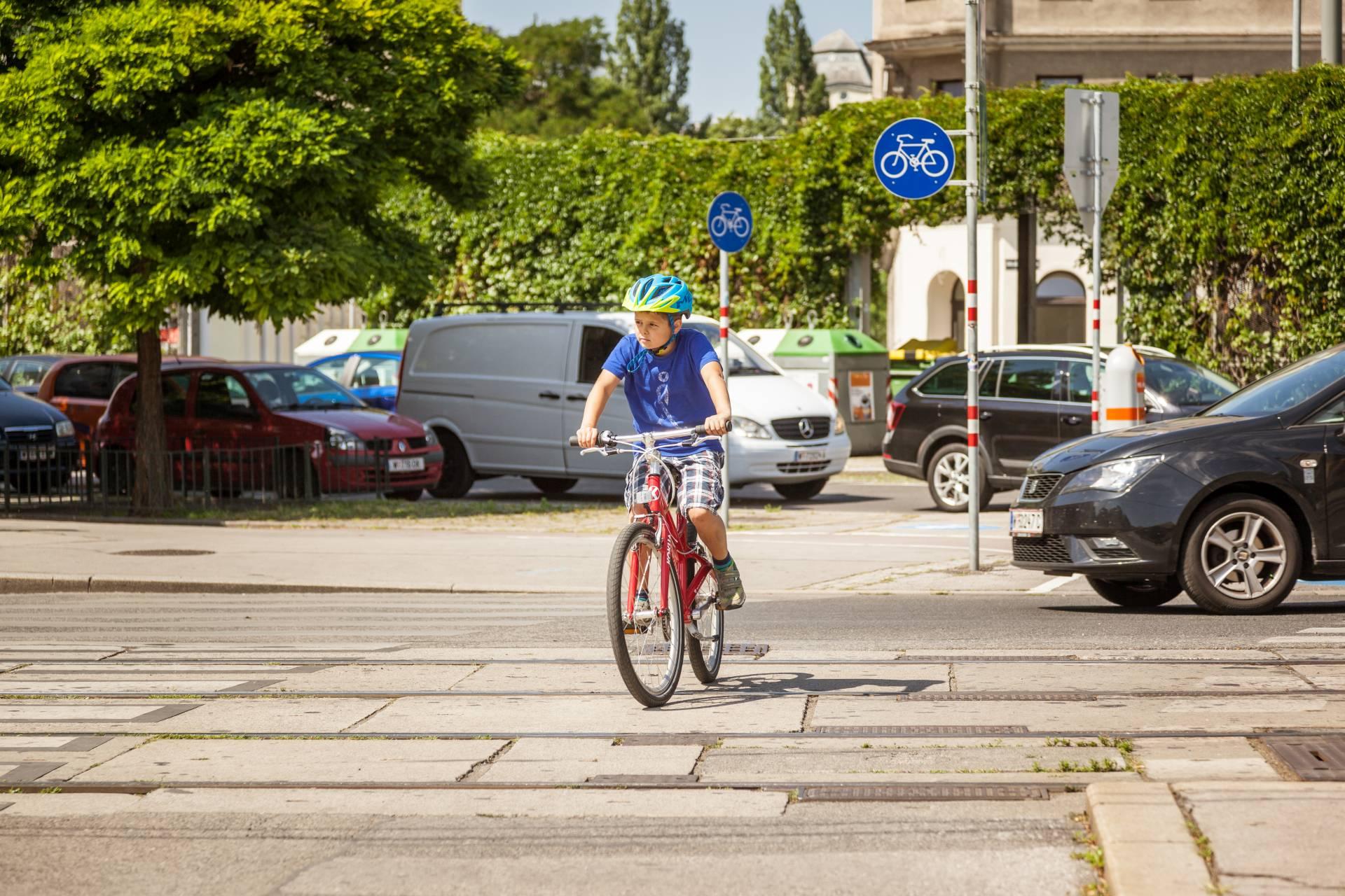 Ein Bub fährt mit dem Fahrrad über eine Kreuzung
