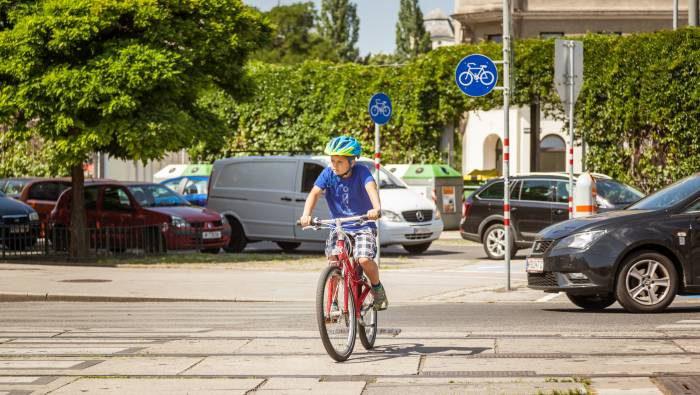 Bub fährt mit dem Fahrrad über eine Kreuzung
