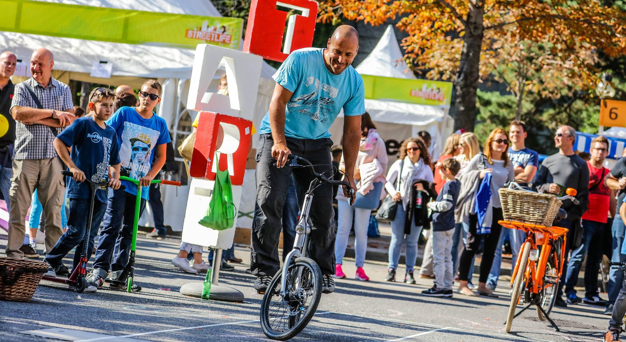 Ein Mann nimmt am Slow Bike Contest beim Streetlife Festival teil. Dabei versucht er so langsam wie möglich auf dem Fahrrad zu fahren ohne das Gleichgewicht zu verlieren.