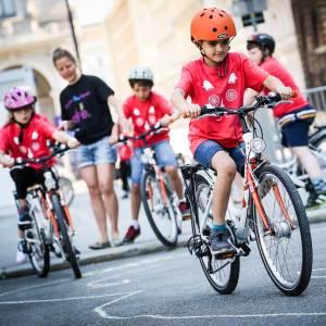 Kinder die beim Radkurs der Mobilitätsagentur spielerisch das Verhalten im Straßenverkehr beigebracht bekommen. Sie fahren mit Fahrrädern in einem Trainings-Parcours und machen Geschicklichkeitsübungen.