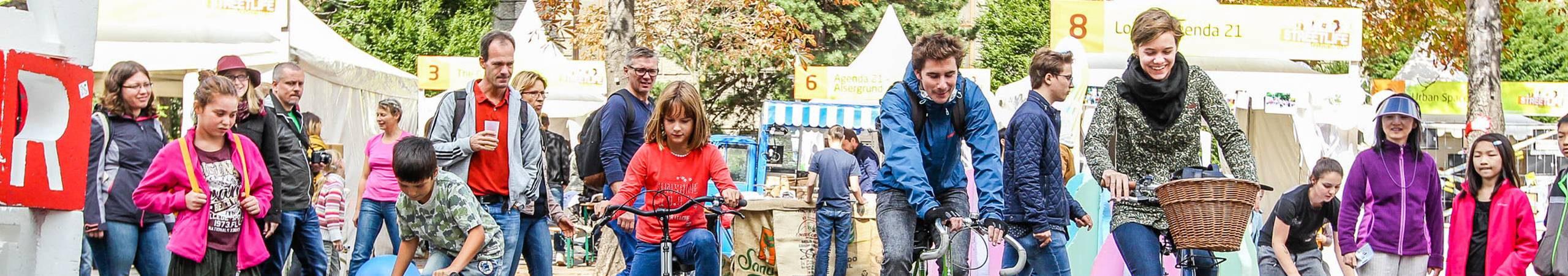 Teilnehmende des Slow Bike Contests beim Streetlife Festival. Sie versuchen mit dem Fahrrad so langsam wie möglich zu fahren ohne das Gleichgewicht zu verlieren