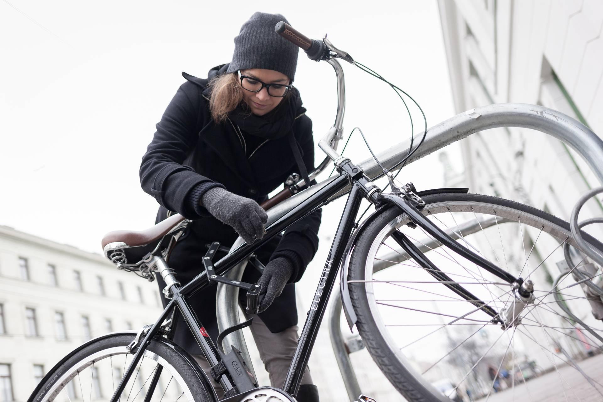 Eine junge Frau befestigt ihr Fahrrad mit Fahrradschloß an einem Fahrradbügel vor der U-Bahn-Station Josefstädterstraße.