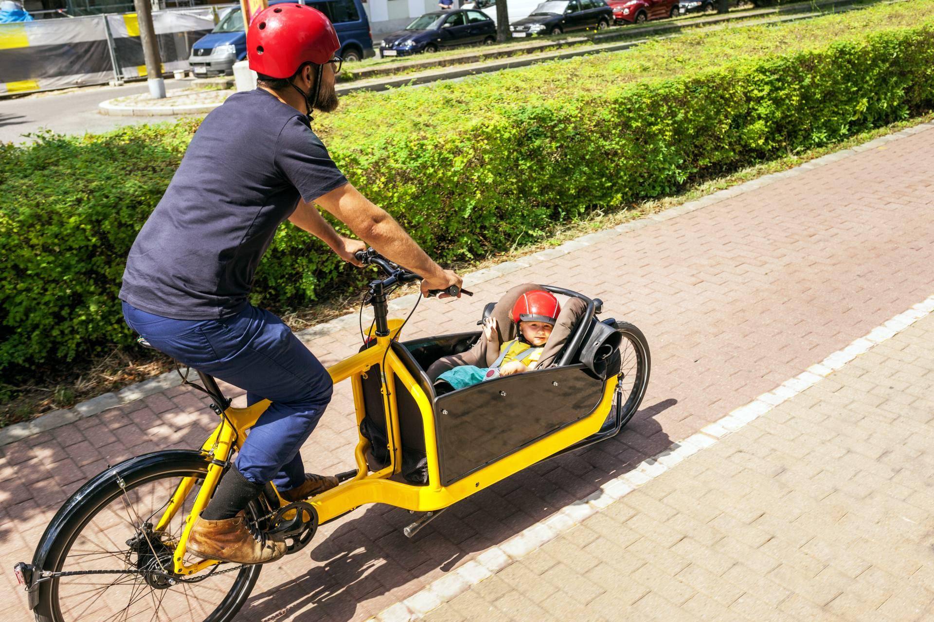 Ein Vater fährt mit einem gelben Lastenrad, im Korb vorne liegt seine 2 Jahre alte Tochter.