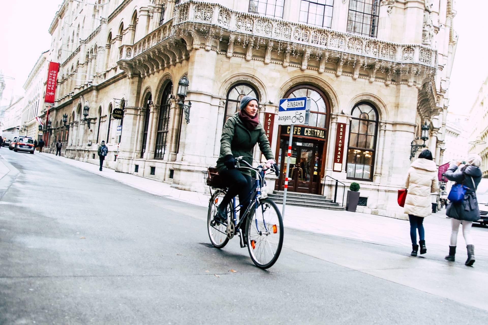 """Eine Frau in einer grünen Jacke fährt entlang einer Straße. Neben ihr deutlich erkennbar ein Einbahnschild mit dem Zusatz """"ausgenommen Fahrräder"""". Foto: Christian Fürthner"""