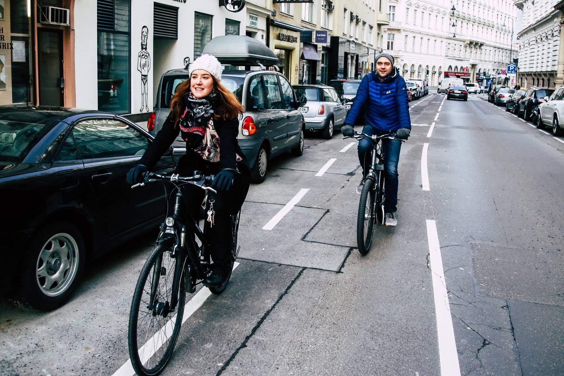 eine Frau mit weißer Mütze und ein Mann mit blauer Jacke fahren hintereinander entlag des Radwegs in der Wipplingerstraße. Foto: Christian Fürthner