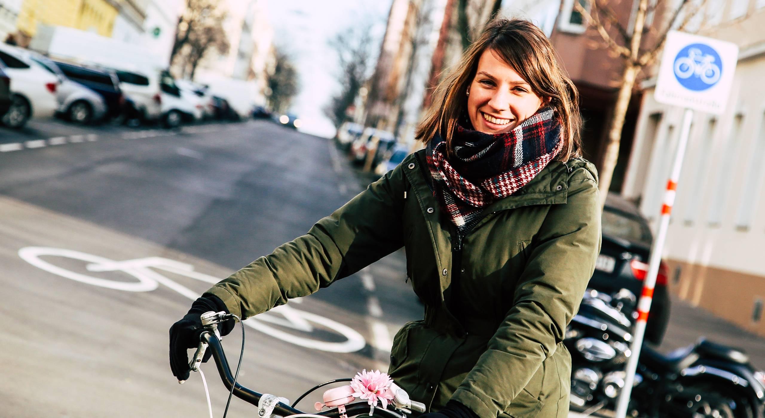 Junge Frau auf dem Fahrrad lächelt in die Kamera. Im Hintergrund sieht man das Schild und das Bodenpiktogramm, die die Fahrradstraße Goldschlagstraße als solche kennzeichnen. Foto: Christian Fürthner