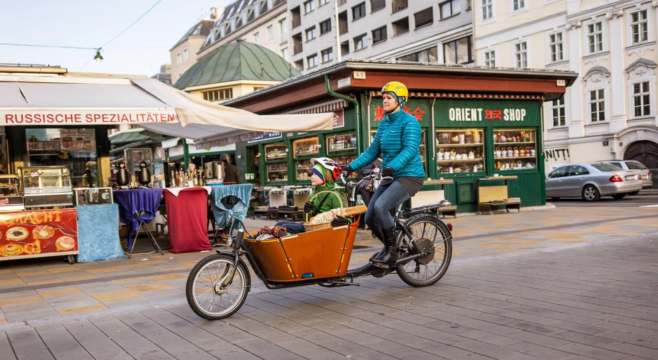 Frau fährt mit Transportfahrrad in der Begegnungszone Schleifmühlbrücke mit dem Naschmarkt im Hintergrund. Ihr kleiner Sohn sitzt im Korb des Transportfahrrads. Foto: Stephan Doleschal