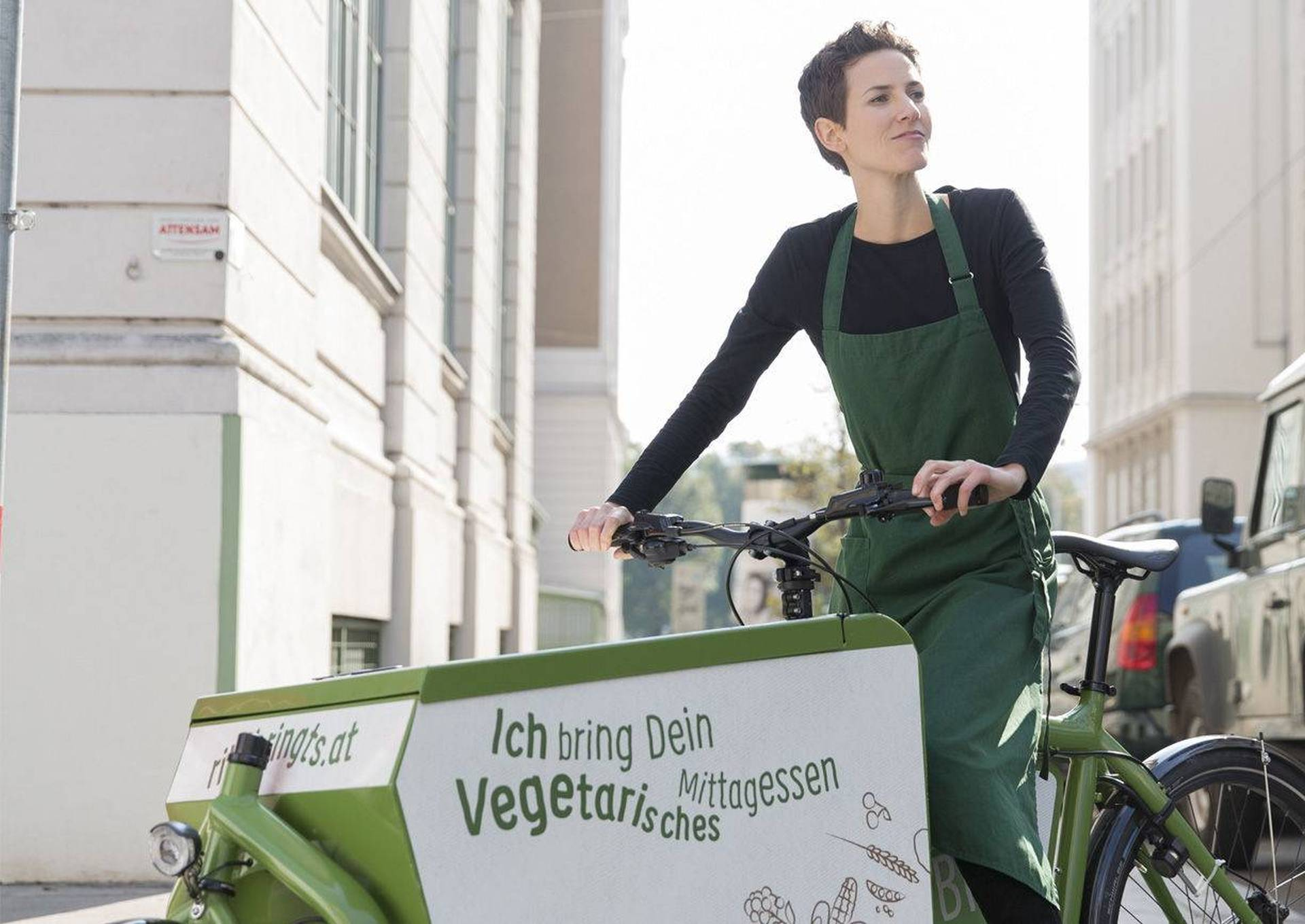 Rita Huber auf einem grünem Transportfahrrad. Foto: ritabringts.at