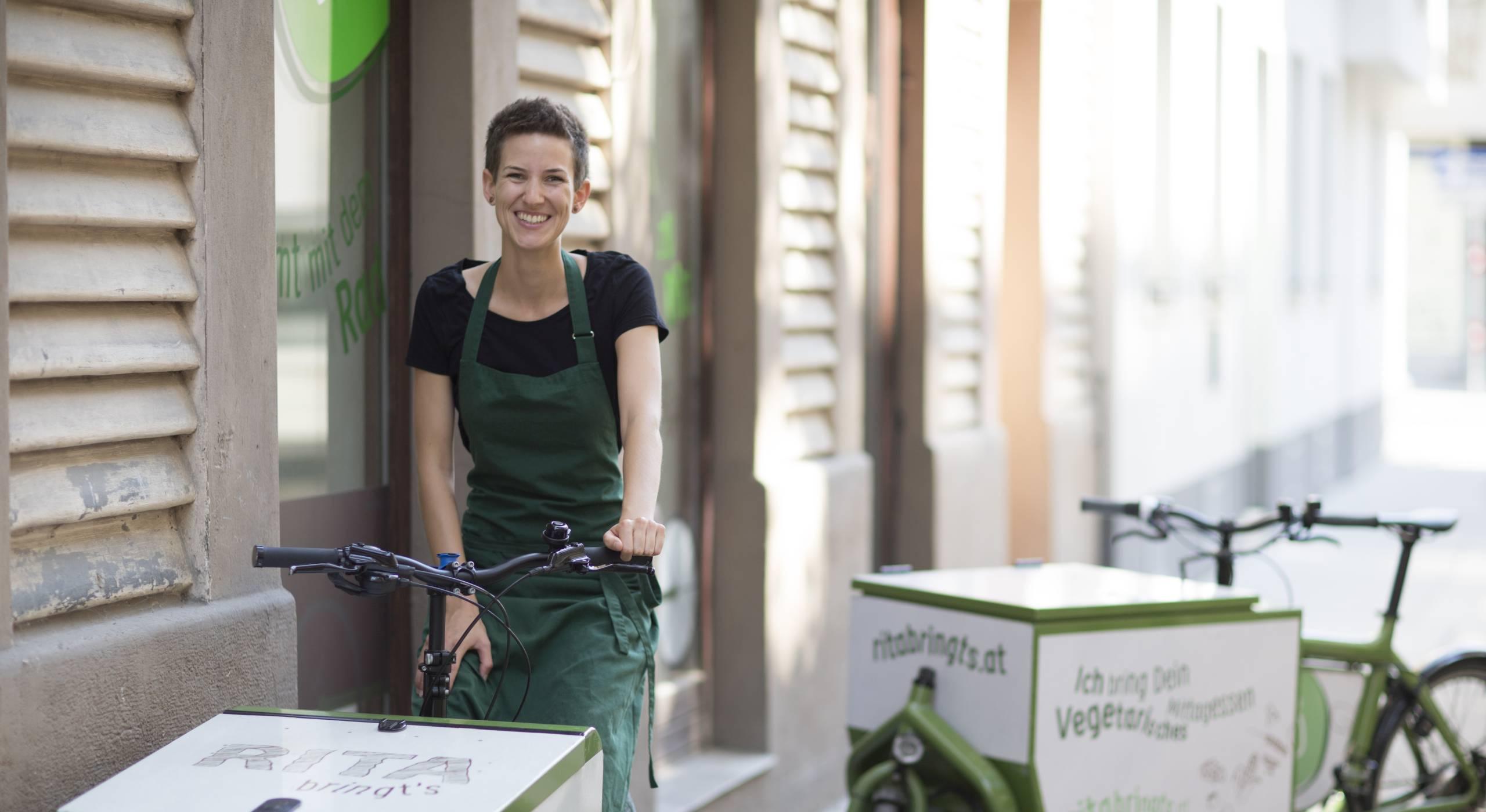 Rita Huber auf einem grünen Transportfahrrad. Foto: ritabringts.at