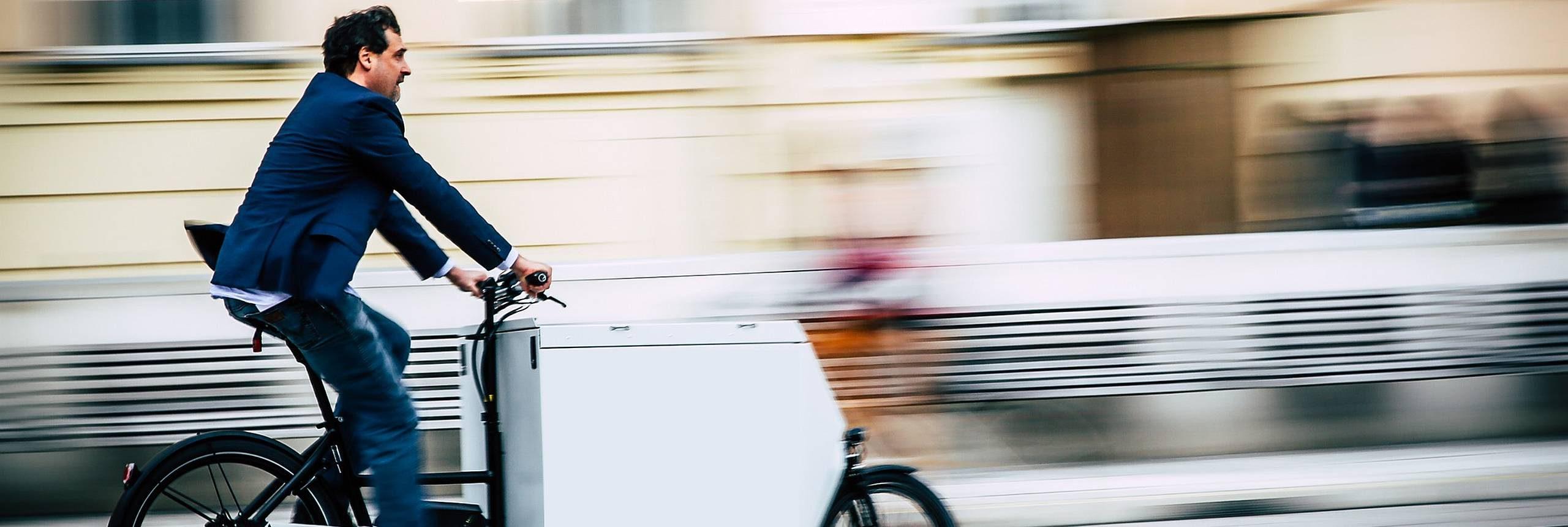 Mann fährt ein Transportfahrrad. Er trägt ein blaues Sakko. Foto: Christian Fürthner