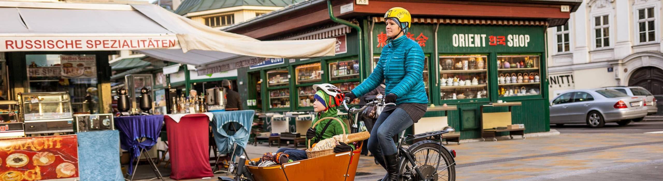 Frau fährt ein Transportfahrrad. Im Korb sitzt ihr Sohn. Foto: Stephan Doleschal