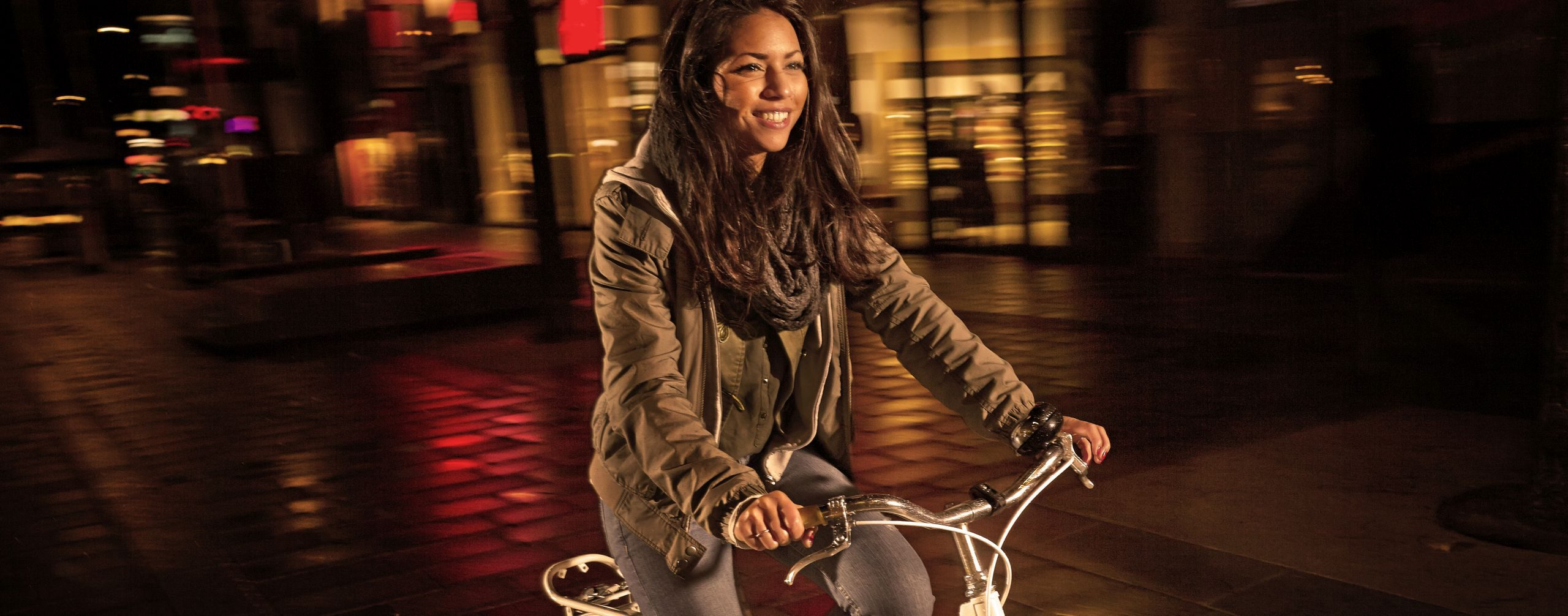 Eine junge Frau ist bei Nacht mit einem gut beleuchteten Fahrrad unterwegs. Foto: Stephan Doleschal
