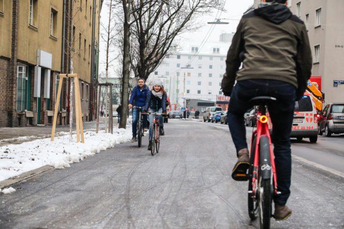 Ein Mann und eine Frau fahren auf dem neuen Radweg entlang der Favoritenstraße, ein Radfahrender kommt ihnen entgegen. Foto aufgenommen von Christian Fürthner.