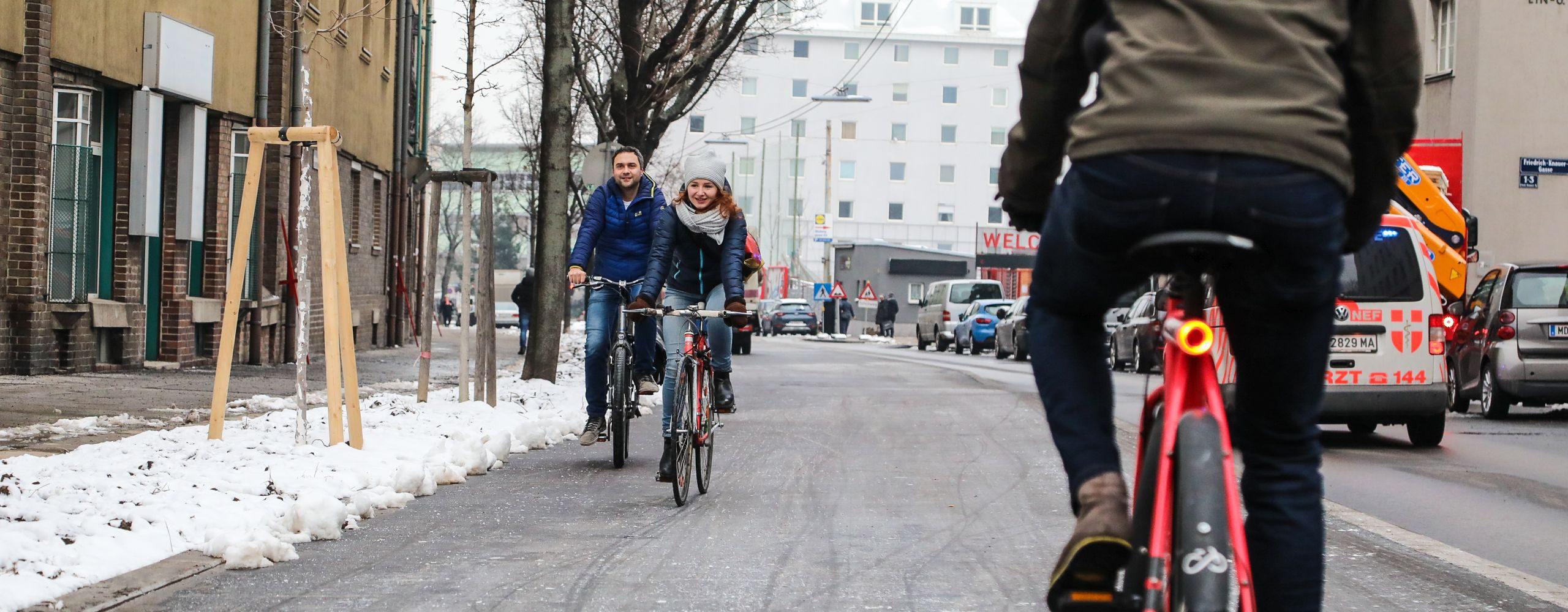 Eine Frau und ein Mann fahren auf dem neuen Radweg entlang der Favoritenstraße, ein Radfahrer kommt ihnen entgegen. Foto aufgenommen von Christian Fürthner