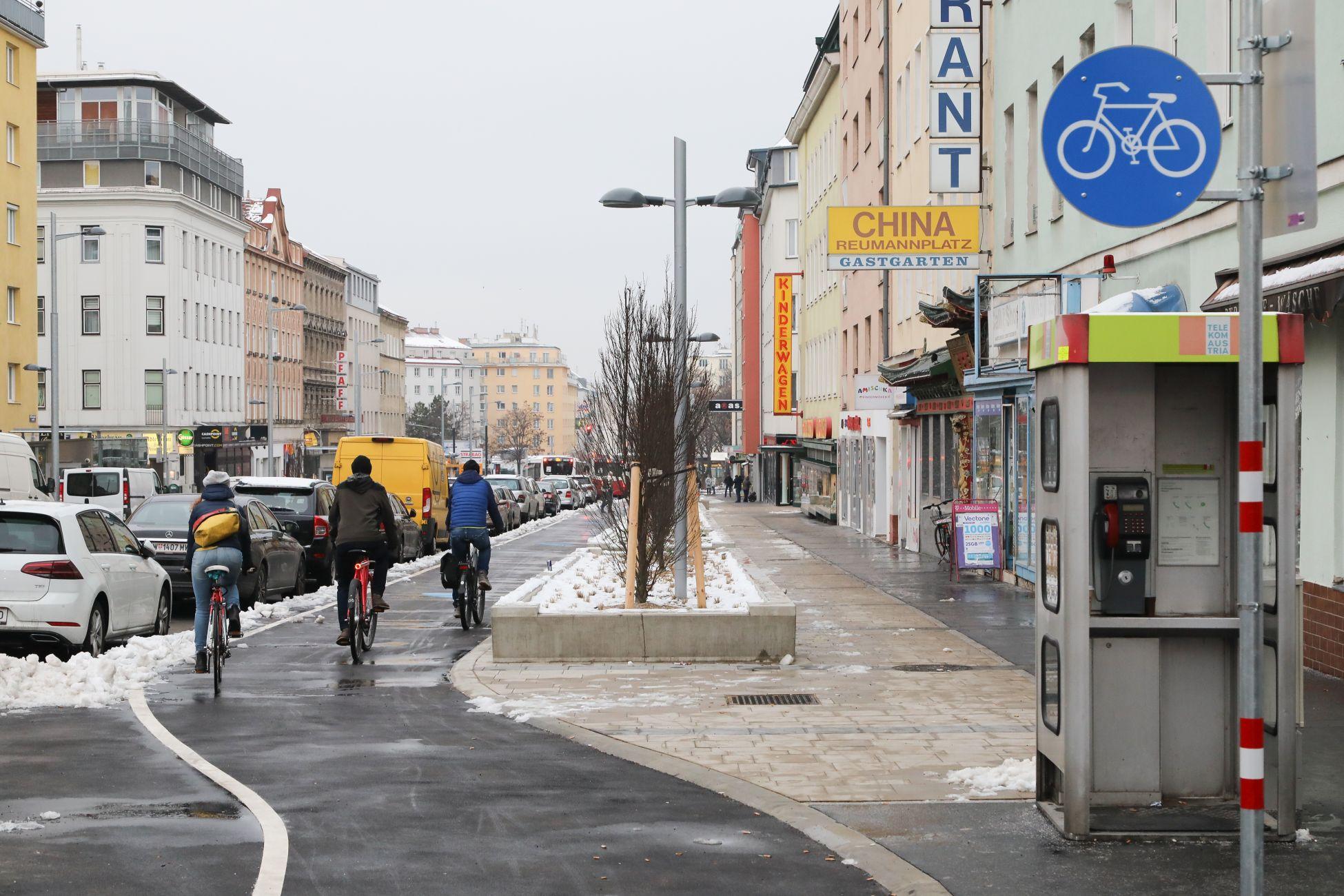 Drei Personen fahren auf dem Radweg entlang der Favoritenstraße, in Richtung Reumannplatz. Man sieht die Personen von hinten. Es ist Winter, am Straßenrand liegt Schnee. Foto aufgenommen von Christian Fürthner.