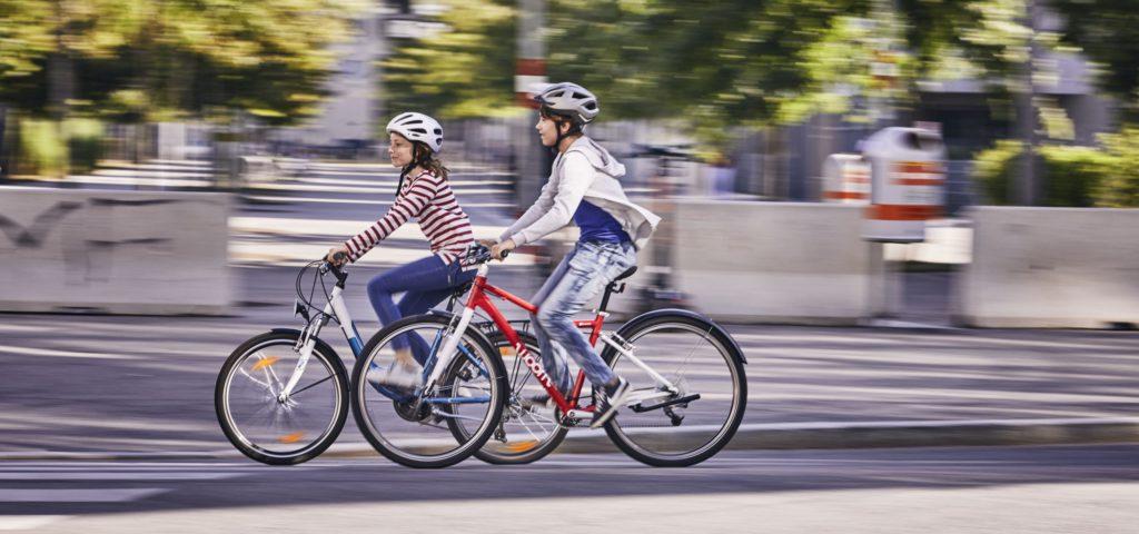 Ein Bub und ein Mädchen fahren mit dem Fahrrad.