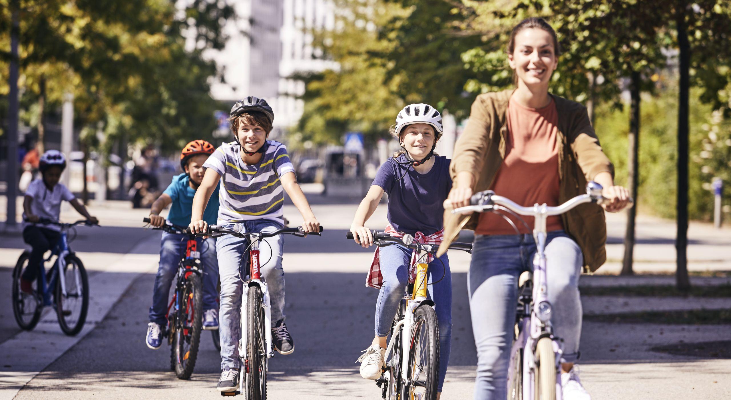 Drei Kinder und eine junge Frau sind gemeinsam auf ihren Fahrrädern unterwegs.