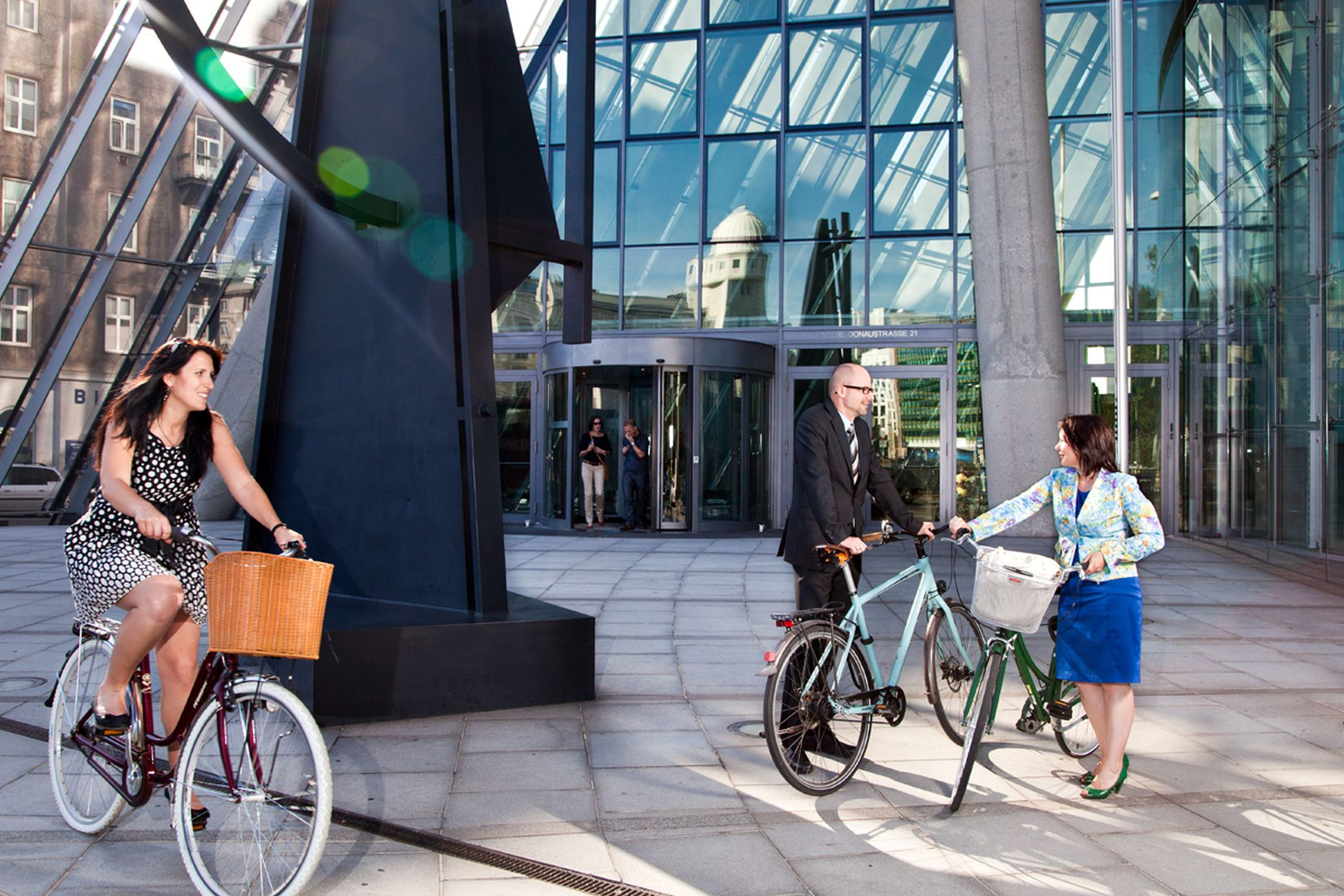 Zwei Frauen und ein Mann auf Fahrrädern vor dem Eingang eines großen Bankgebäudes.