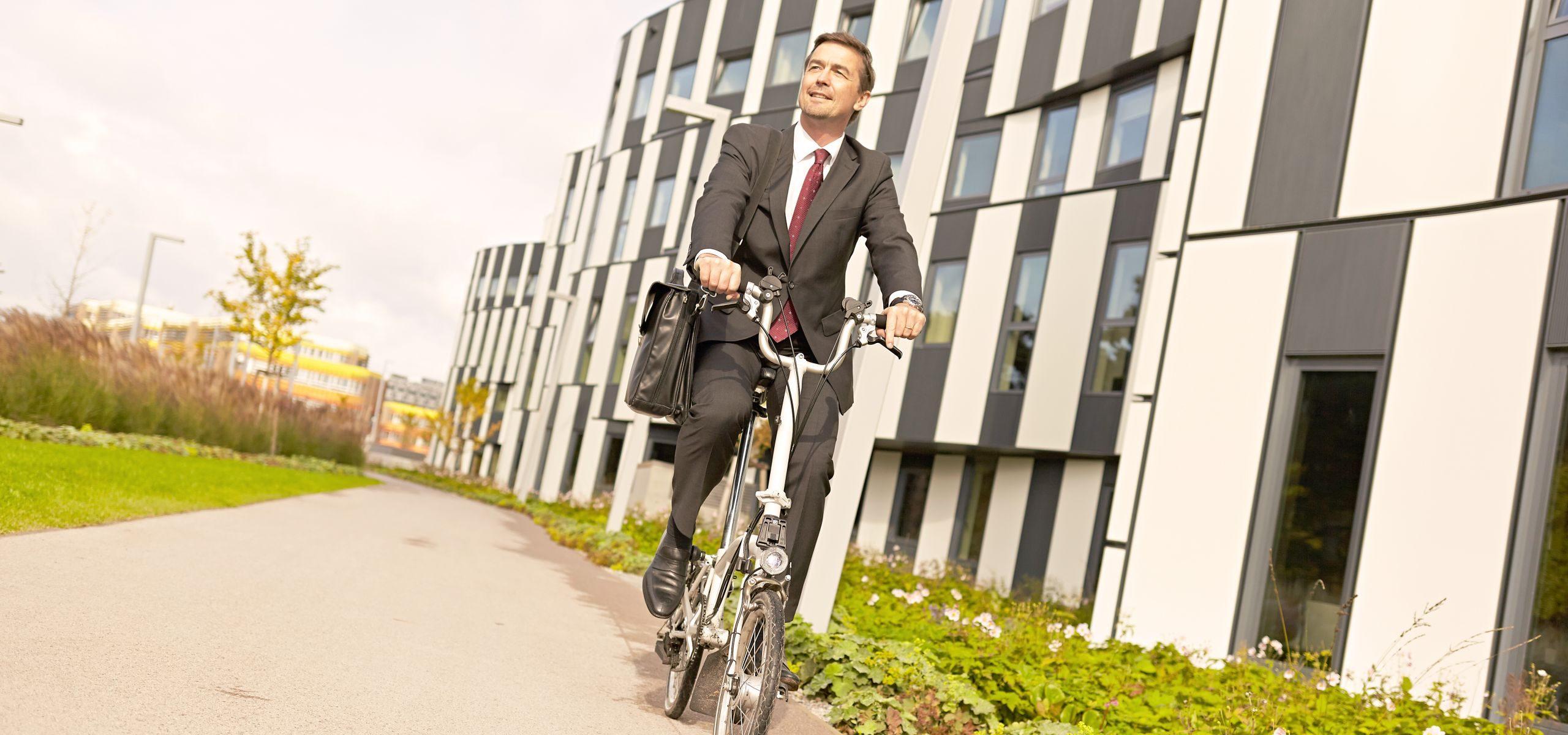Mann fährt auf seinem Klapprad an einem modernen Gebäude am WU Caampus vorbei.