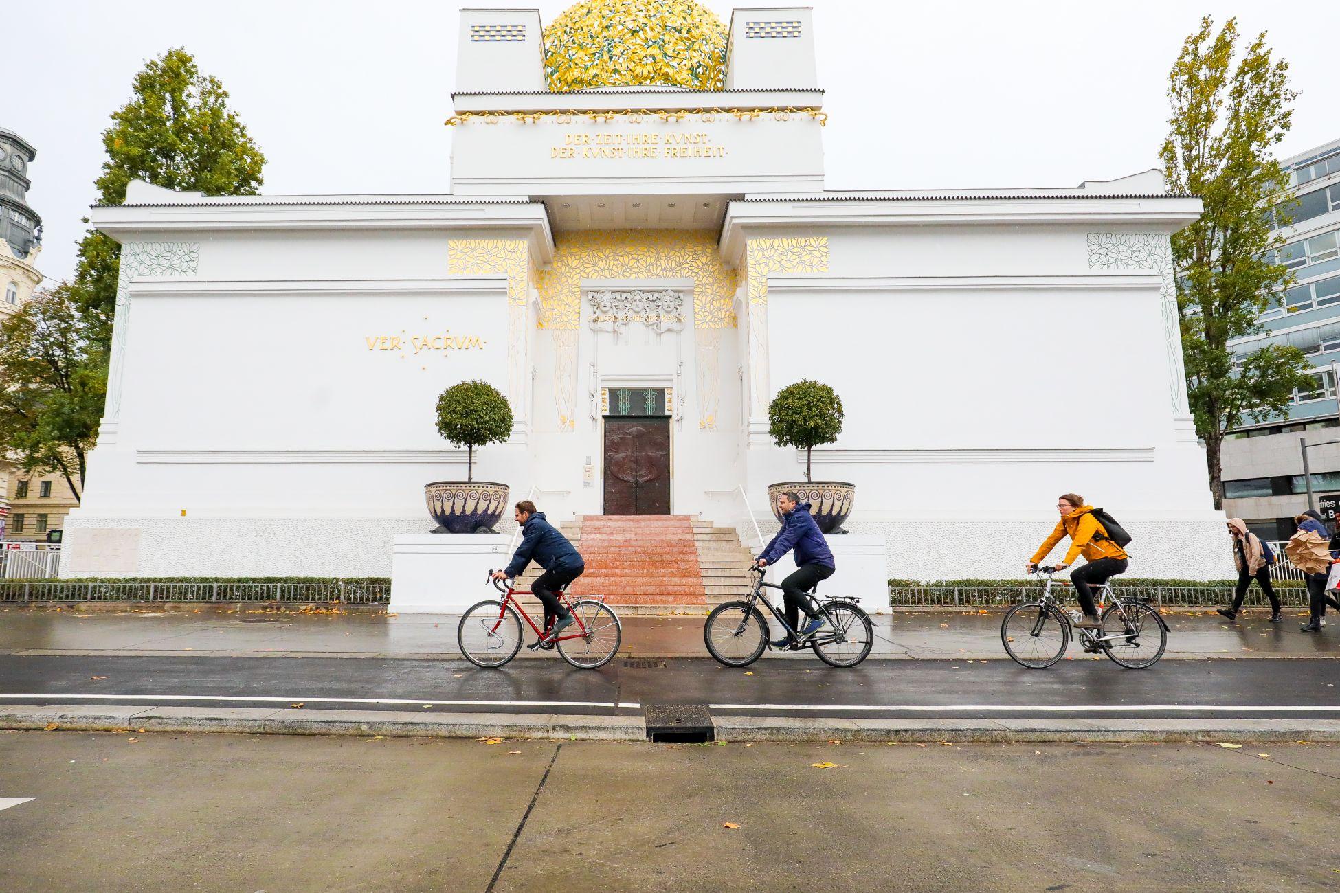 Drei Radler fahren am neuen Radweg enmtlang der Linken Wienzeile an der Secession vorbei.