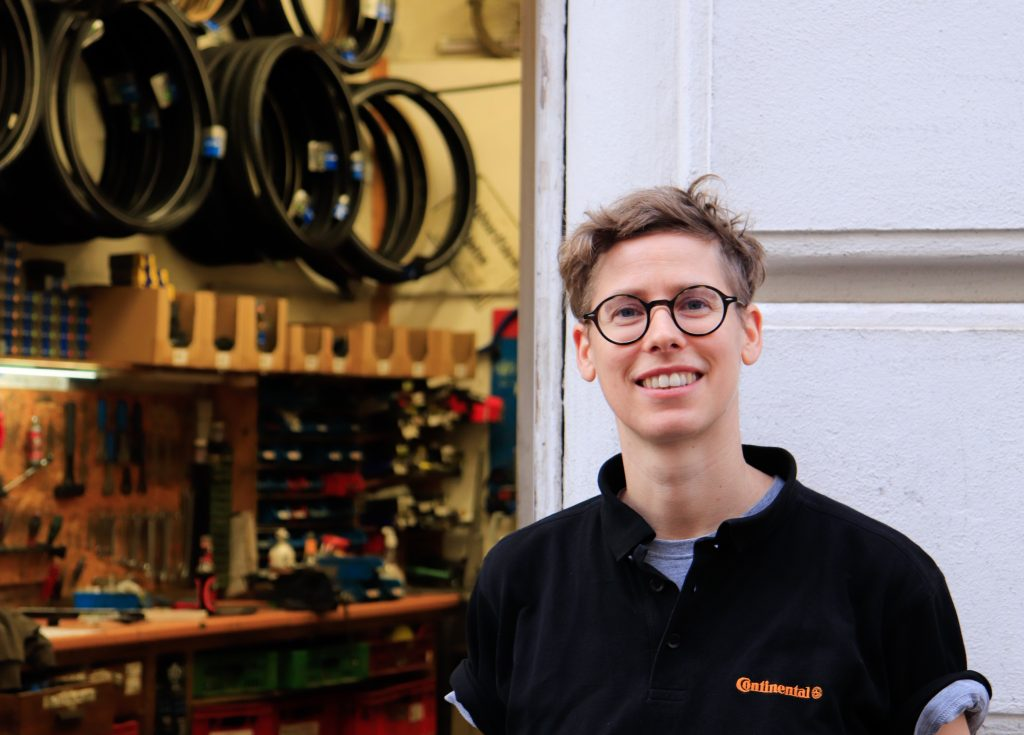Pez steht vor der Fahrradwerkstatt, durch die offene Tür sieht man Reifen, die an der Wand hängen und verschiedene Werkzeuge auf einem langen Tisch
