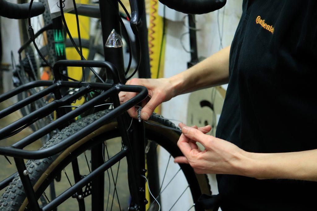 Pez Hände in Großaufnahme, die eine Fahrradschaltung reparieren