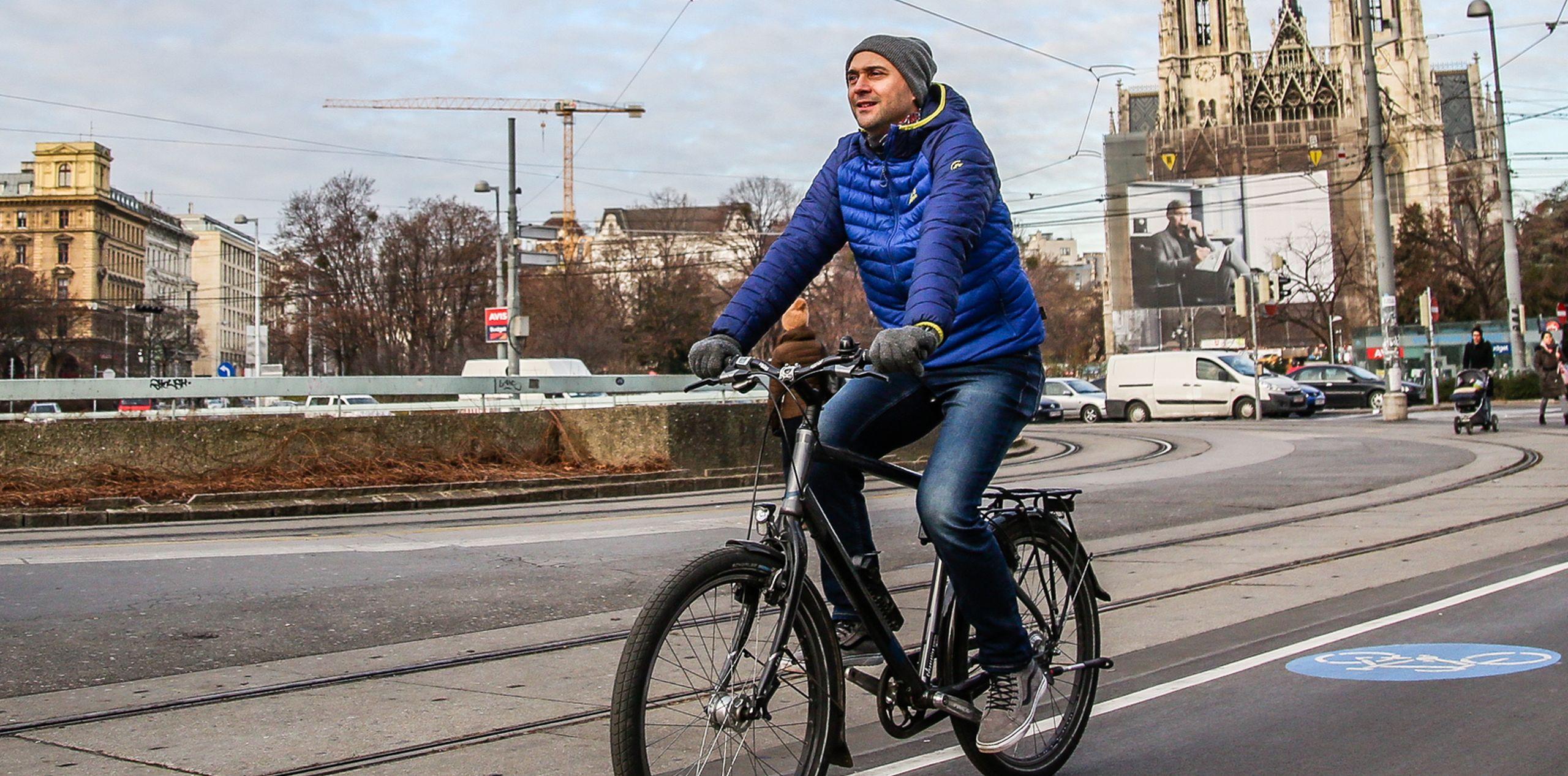 Radfahrer radelt entlang des Radwegs am Schottenring. Im Hintergrund sieht man die Votivkirche.
