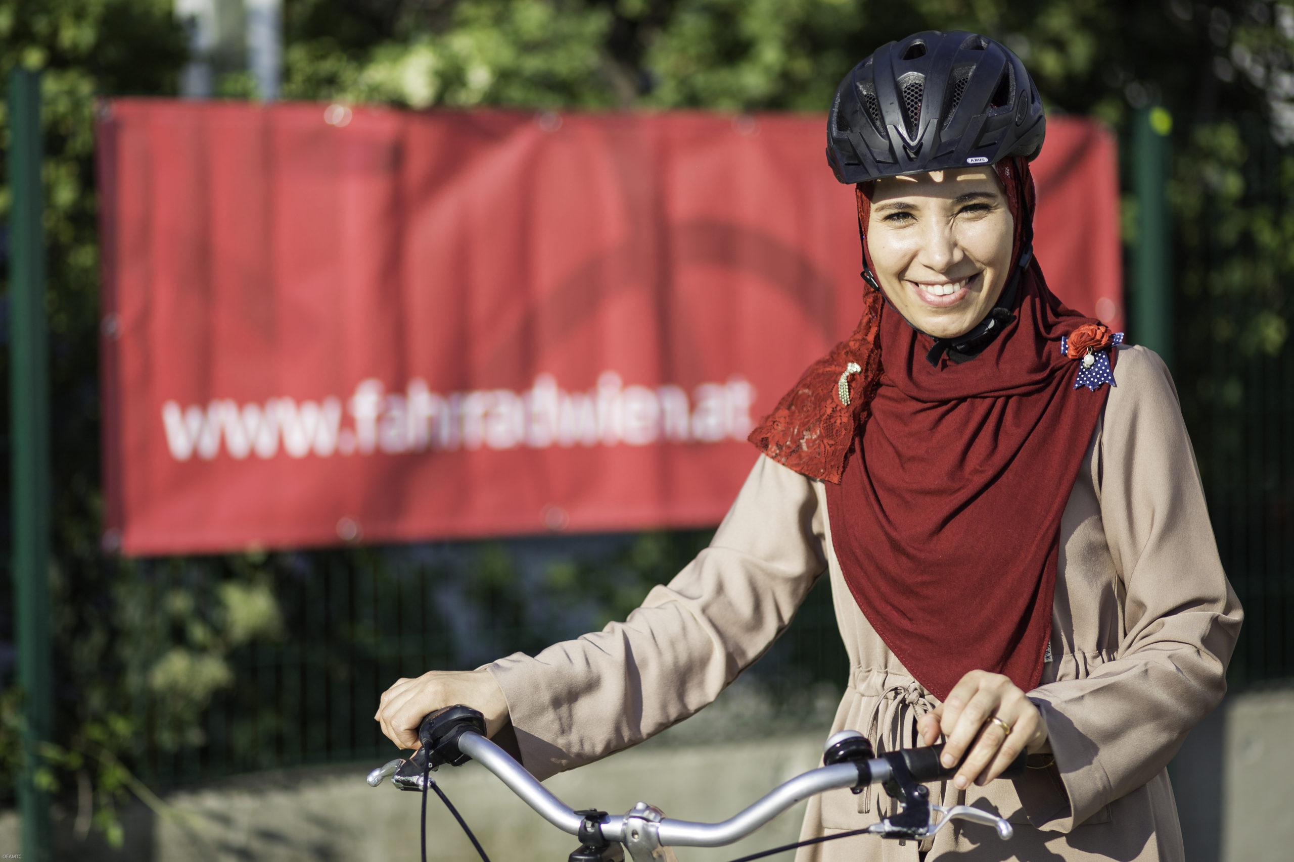 Eine Frau mit einem Schleier und Helm steht mit ihrem Fahrrad und lächelt in die Kamera