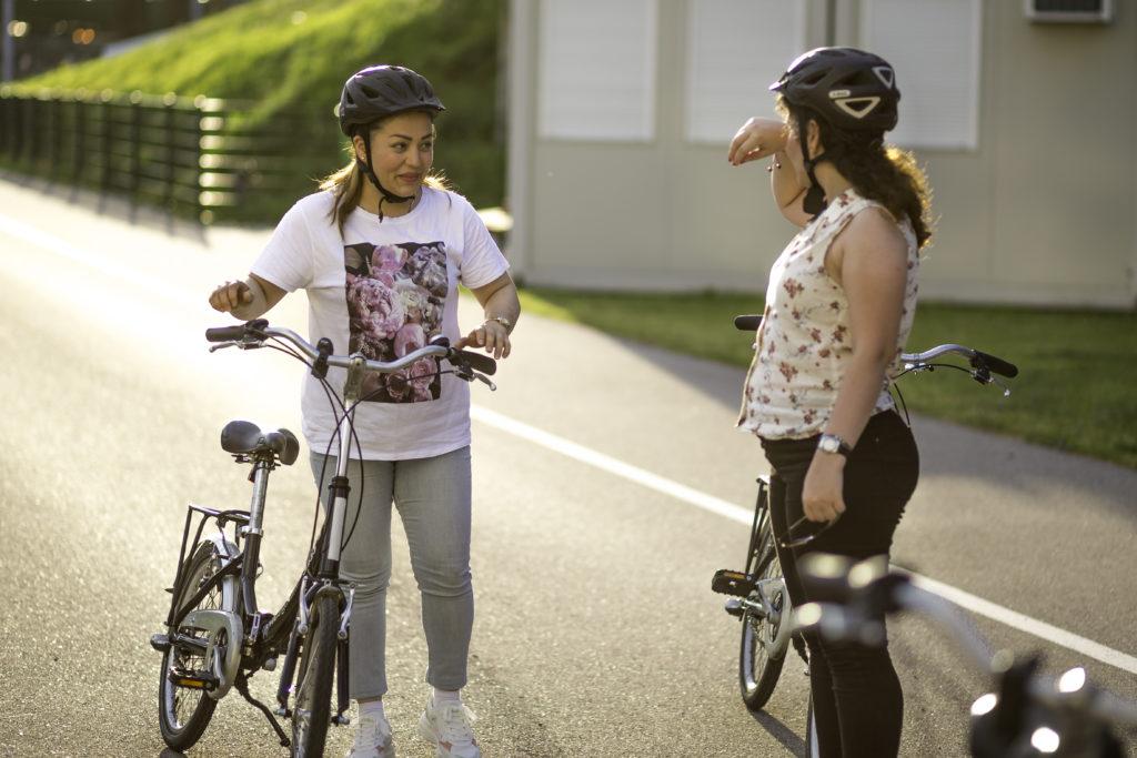Zwei Frauen mit Fahrrädern stehen sich gegenüber