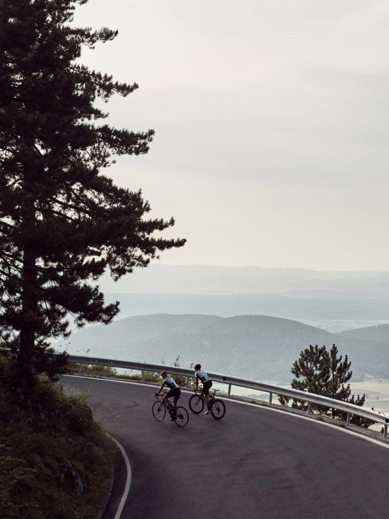 Nora und eine anderer Rennradfahrer fahren auf einer Bergstraße um die Kurve, im Hintergrund hügelige Landschaft