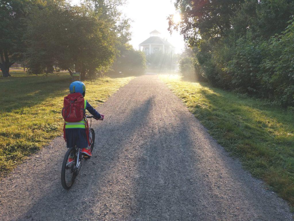 Ein Kind fährt mit einem Fahrrad einen Weg entlang. Es ist von hinten zu sehen.