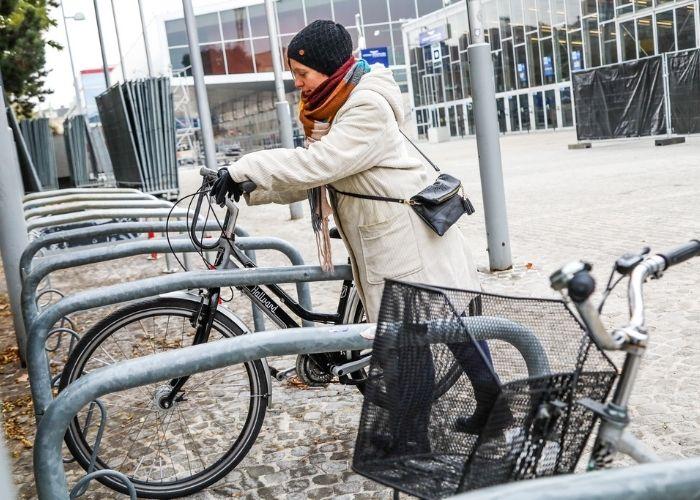Radfahrerin stellt ihr Fahrrad im Radständer vor der Wiener Stadthalle ab.