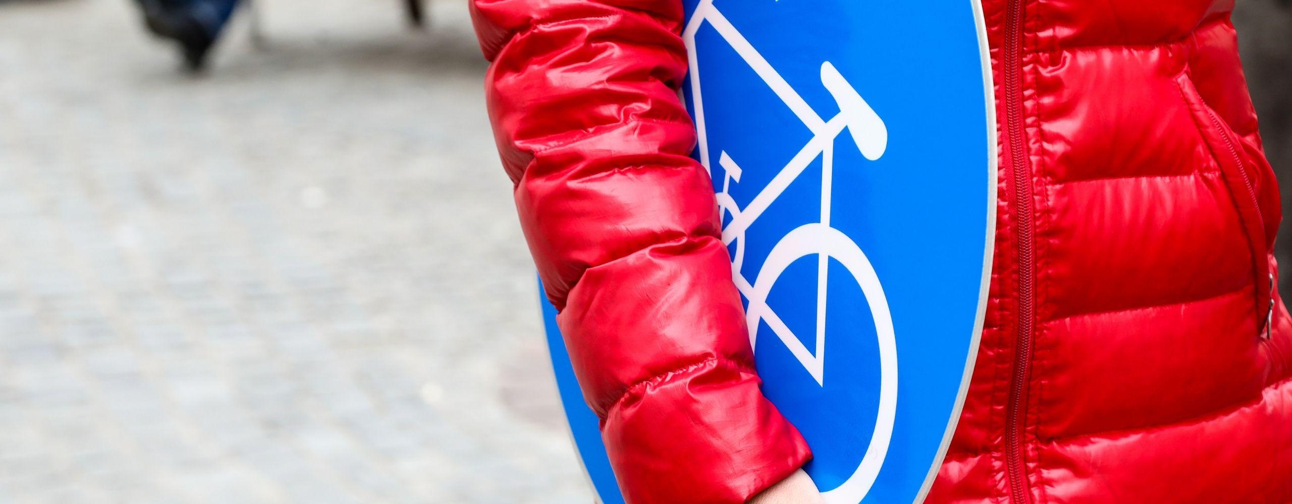 Frau hält Radwegschild, © PID/Christian Fürthner