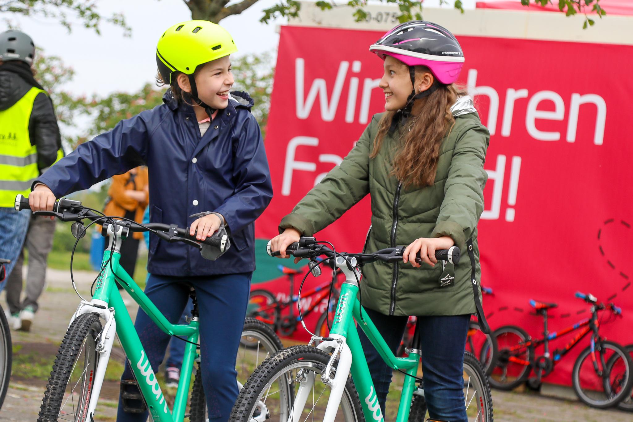zwei lachende Kinder auf Fahrrädern