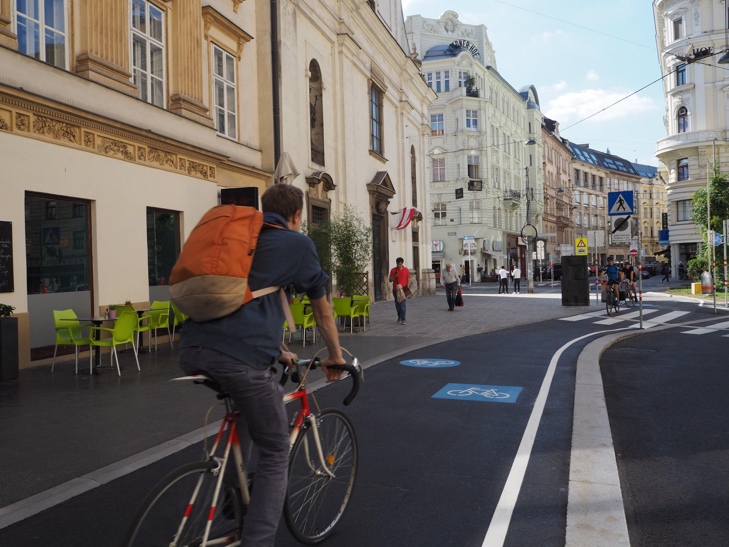 Radfahrende am neuen Radweg vor der Paulanerkirche